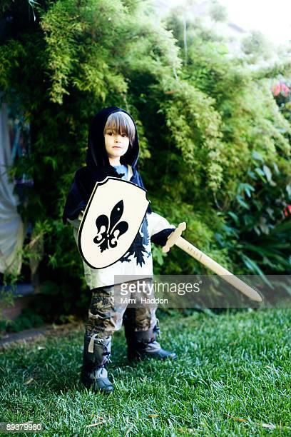 4 Year Old Boy Dressed As Knight in Backyard