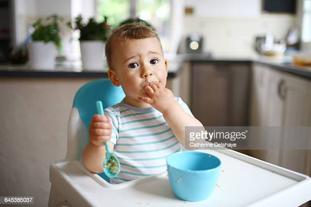 A 1 year old boy eating in his high chair