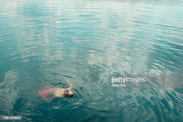15 year old boy floating in turquoise water