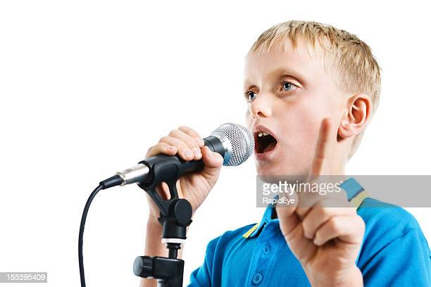 9 year old boy giving a serious speech into microphone