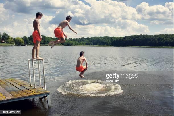 15 year old boy going for a swim in lake in bright orange swim trunks