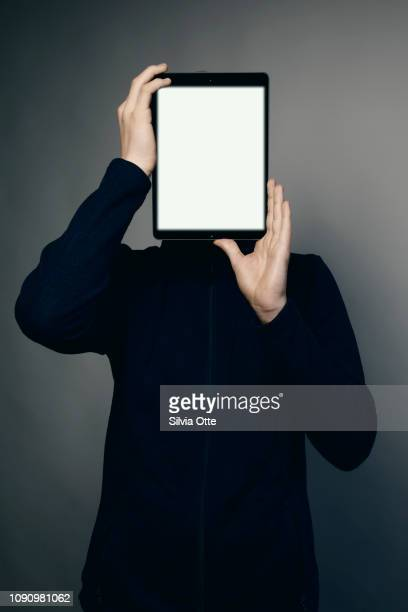 15 year old boy holding tablet in front of his face