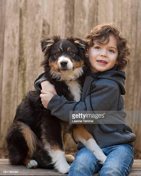 4 year old boy hugging Australian Shepherd dog