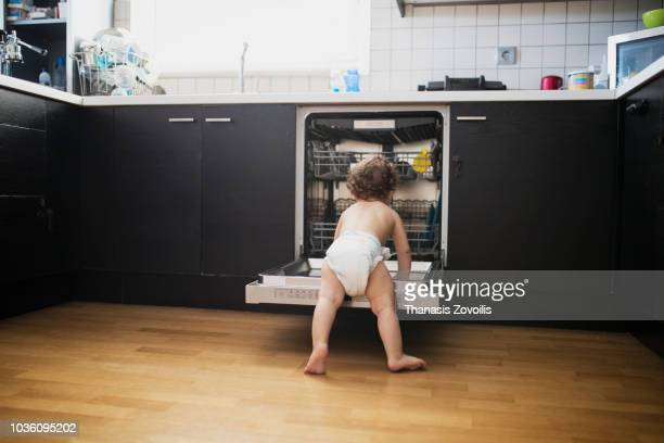 1 year old boy in front of a dishwasher