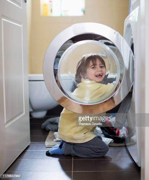 4 year old boy in front of a washing machine