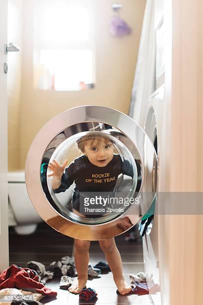 1 year old boy in front of washing machine - waschmaschine stock-fotos und bilder