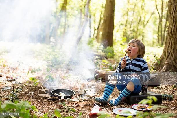 a 3 year old boy in the woods eating a sausage. - snag tree stock pictures, royalty-free photos & images