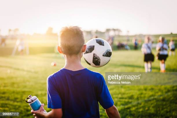 11 year old boy juggling soccer ball while walking off soccer field - clubvoetbal stockfoto's en -beelden