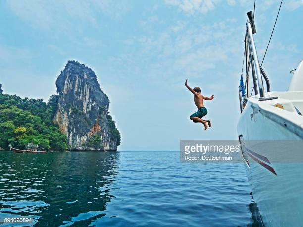 8 year old boy jumping from sailboat in Thailand while on vacation