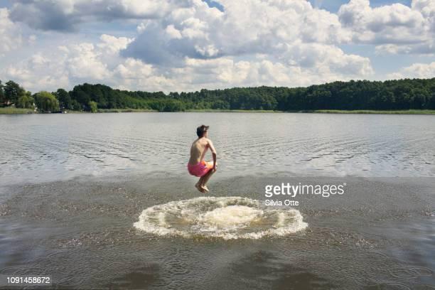 15 year old boy jumping in lake in bright orange swim trunks