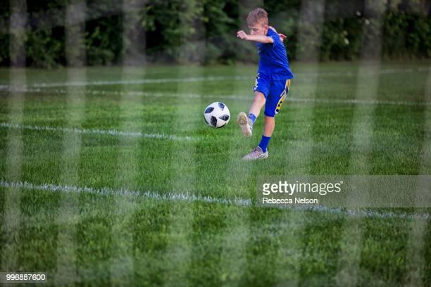 11 year old boy kicking soccer into goal shot through net