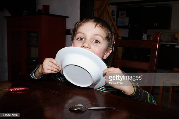 5 year old boy licking his plate