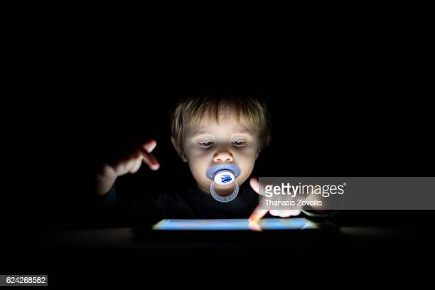 1 year old boy looking a digital tablet in the dark