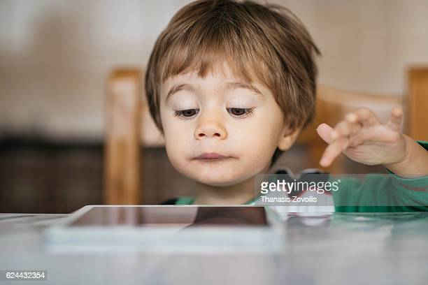 1 year old boy looking a digital tablet - human body part stock pictures, royalty-free photos & images