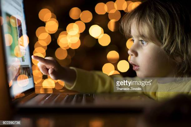 2 year old boy looking a laptop in the dark - display digital - fotografias e filmes do acervo