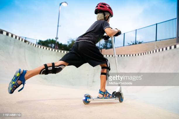a 7 year old boy on a scooter at the skate park - carlsbad california stock pictures, royalty-free photos & images