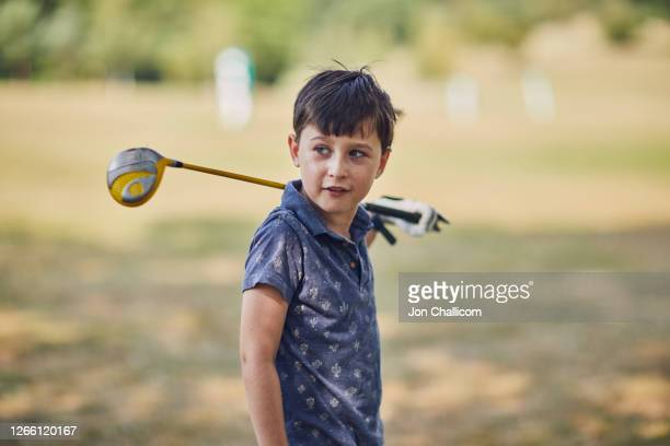 a 7 year old boy poses with a golf club - golf stock pictures, royalty-free photos & images