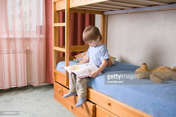 5 year old boy sits on bunk  bed reading a book