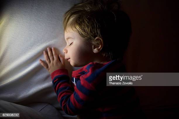 2 year old boy sleeping in a dark room