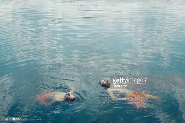 15 year old boy swimming in blueish lake water