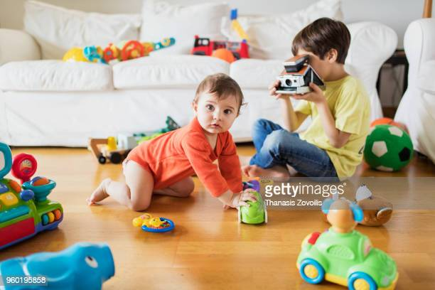 7 year old boy taking photo of his brother