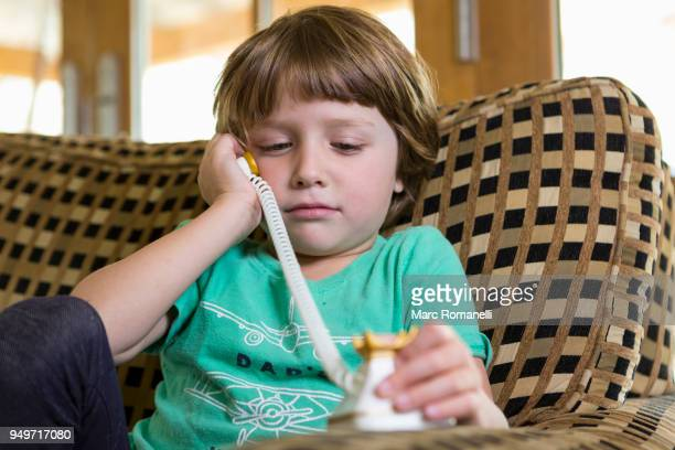 4 year old boy talking on toy telephone