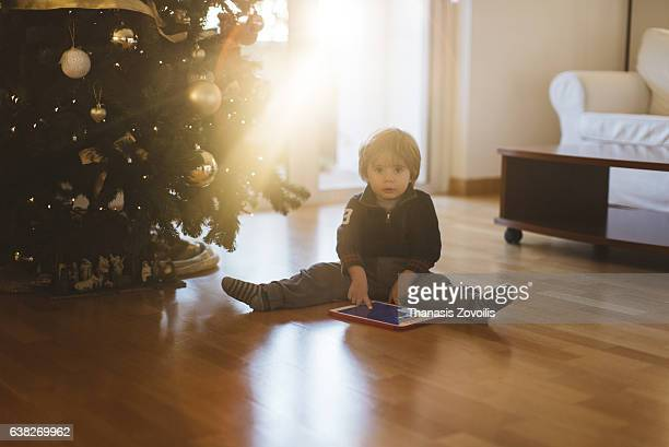 2 year old boy using a digital tablet in front of a christmas tree