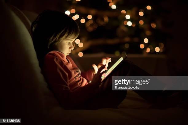 5 year old boy using a digital tablet in the dark