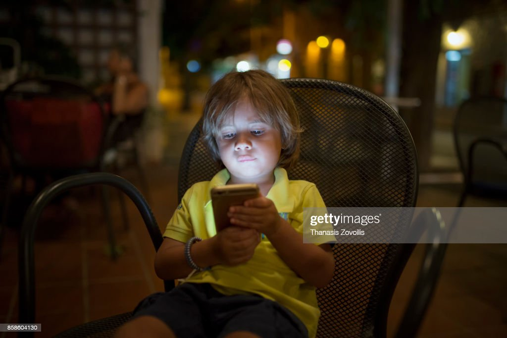 2 year old boy using a digital tablet outdoor : Stock-Foto