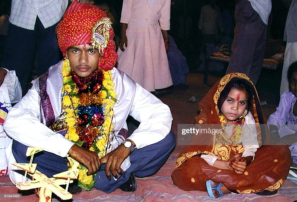 A 16 year old boy (L) waits to be married to a much younger girl (R) during a mass child marriage ceremony in Indore, 15 May 2002 some 200 kms west of the Madhya Pradesh state capital city Bhopal. At least 140 children aged 4 to 17 years took part in mass wedding ceremonies despite a government ban on under-age nuptials.