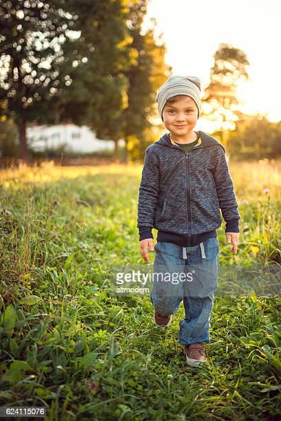 4 year old boy walk through a meadow