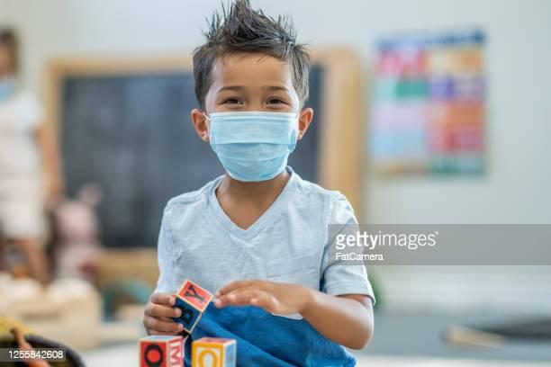 5 歲男孩在托兒所戴著面具 - 出席 個照片及圖片檔
