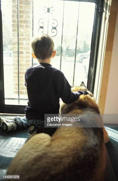 Year Old Boy With Dog Looking Out Door