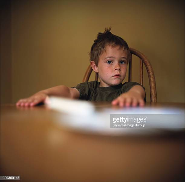7 year old boy with messy hair sat at table with plate 29/05/03
