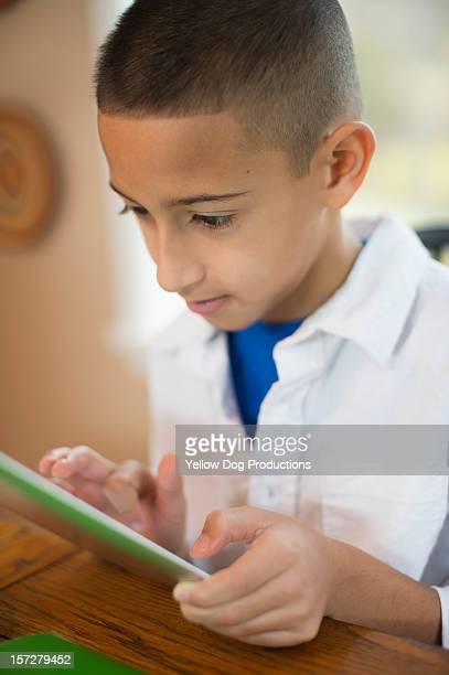 9 year old boy working on digital tablet