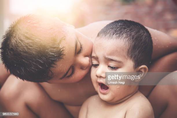 5 year old brother kissing her toddler sister - indian girl kissing stock photos and pictures