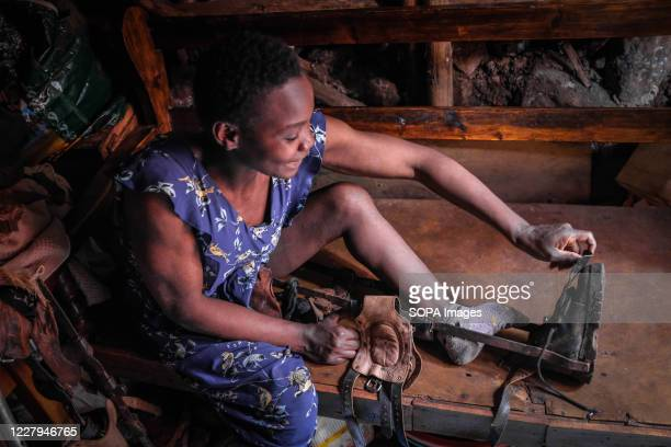 Year old Cecilia Atieno a disabled single mother, born with both legs paralysed seen putting on her shoes for work during the pandemic. Persons with...