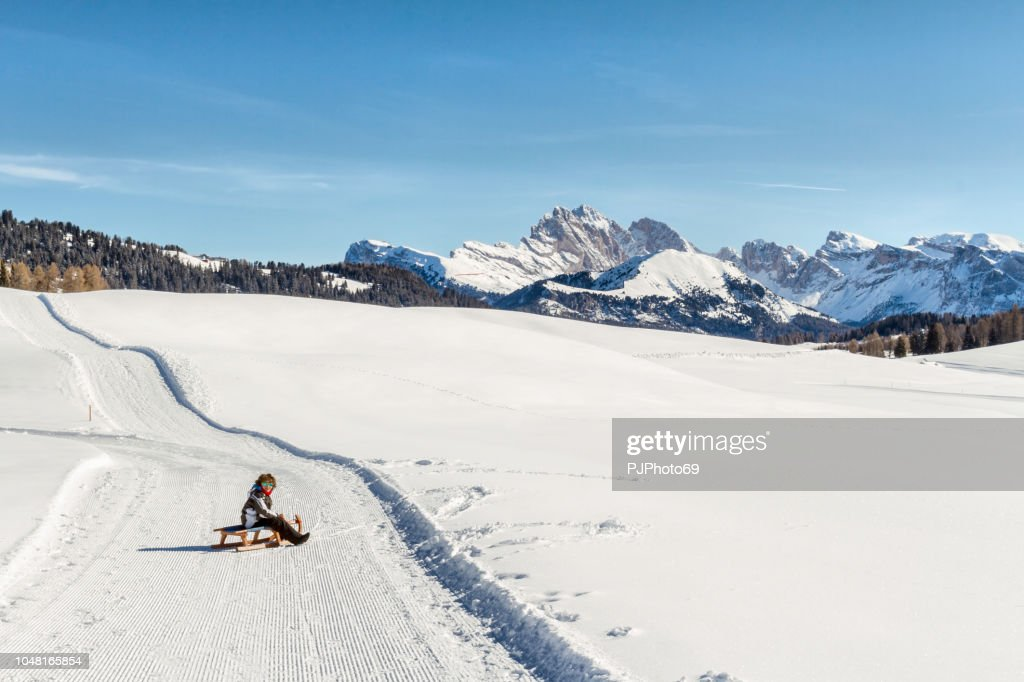 7 year old child on a sled in the Dolomites - Seiser Alm : Foto stock