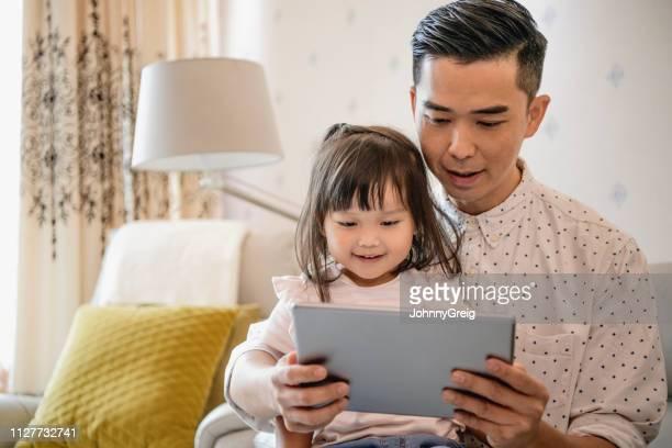 父とタブレットを使用して 4 歳の中国の女の子