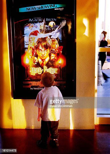 3 year old Christian Robb of Centennial Colorado stares up at the movie poster announcing Harry Potter and Sorcerer's Stone is now showing at United...