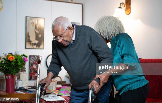 62 year old daughter helping her 91 tear old father to stand up from his chair - 63 year old female stock pictures, royalty-free photos & images