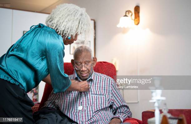 62 year old daughter helping her 91 year old father with his shirt - lucy lambriex stockfoto's en -beelden