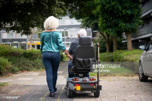 62 year old daughter walking next to 91 year old father in mobility scooter - electric scooter stock pictures, royalty-free photos & images