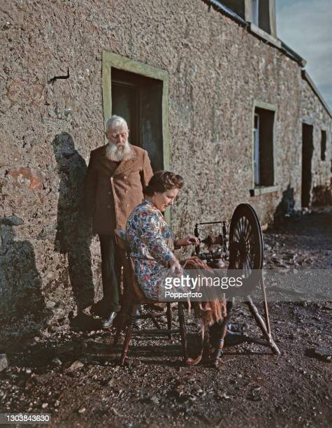Year old Donald Morrison looks on as his widowed daughter Mrs MacGeddie spins Harris Tweed on a spinning wheel outside the family's croft cottage on...