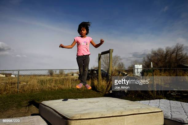 6 year old Dreamer Bravehawk has the mattress all to her self as she bounces in her grandfathers backyard in Ethete on the Wind River Indian...
