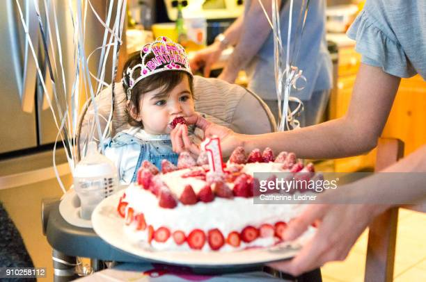 1 year old eating strawberry from birthday cake - happybirthdaycrown stock pictures, royalty-free photos & images