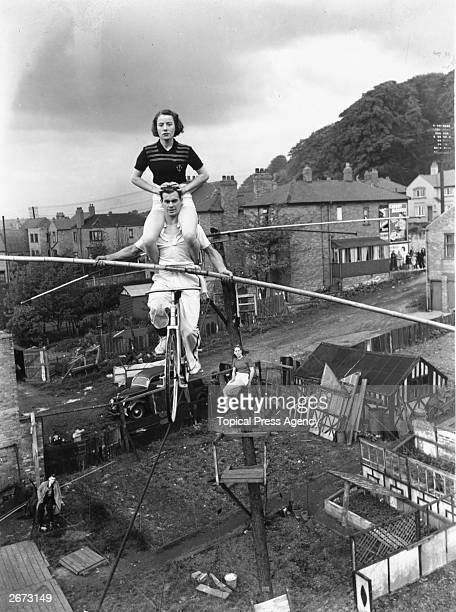 15 year old Elsie Davis practising a balancing act above her garden with her father and brother who have left their jobs as miners to join a circus