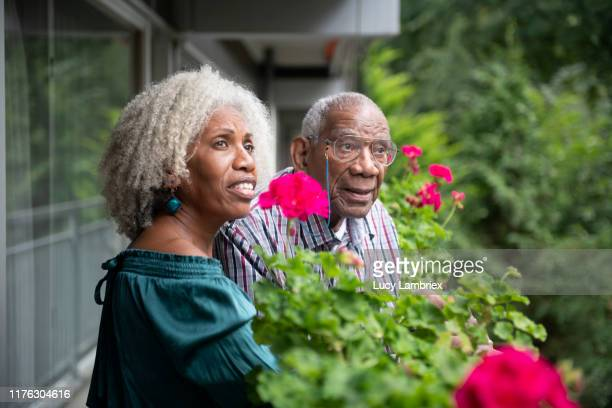 91 year old father and his 62 year old daughter standing on his balcony and looking at the surroundings - 63 year old female stock pictures, royalty-free photos & images