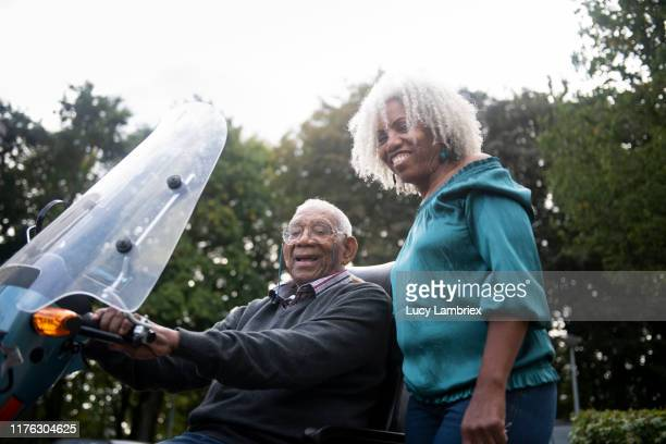 91 year old father on mobility scooter and 62 year old daughter posing outdoors - 63 year old female stock pictures, royalty-free photos & images
