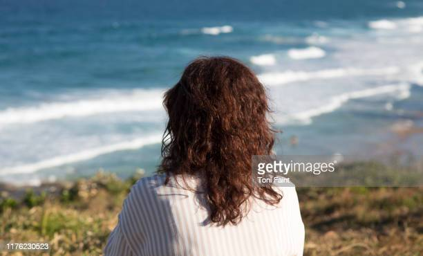 a 53 year old female looking on a hill looking out to sea - espalda chica morena playa fotografías e imágenes de stock